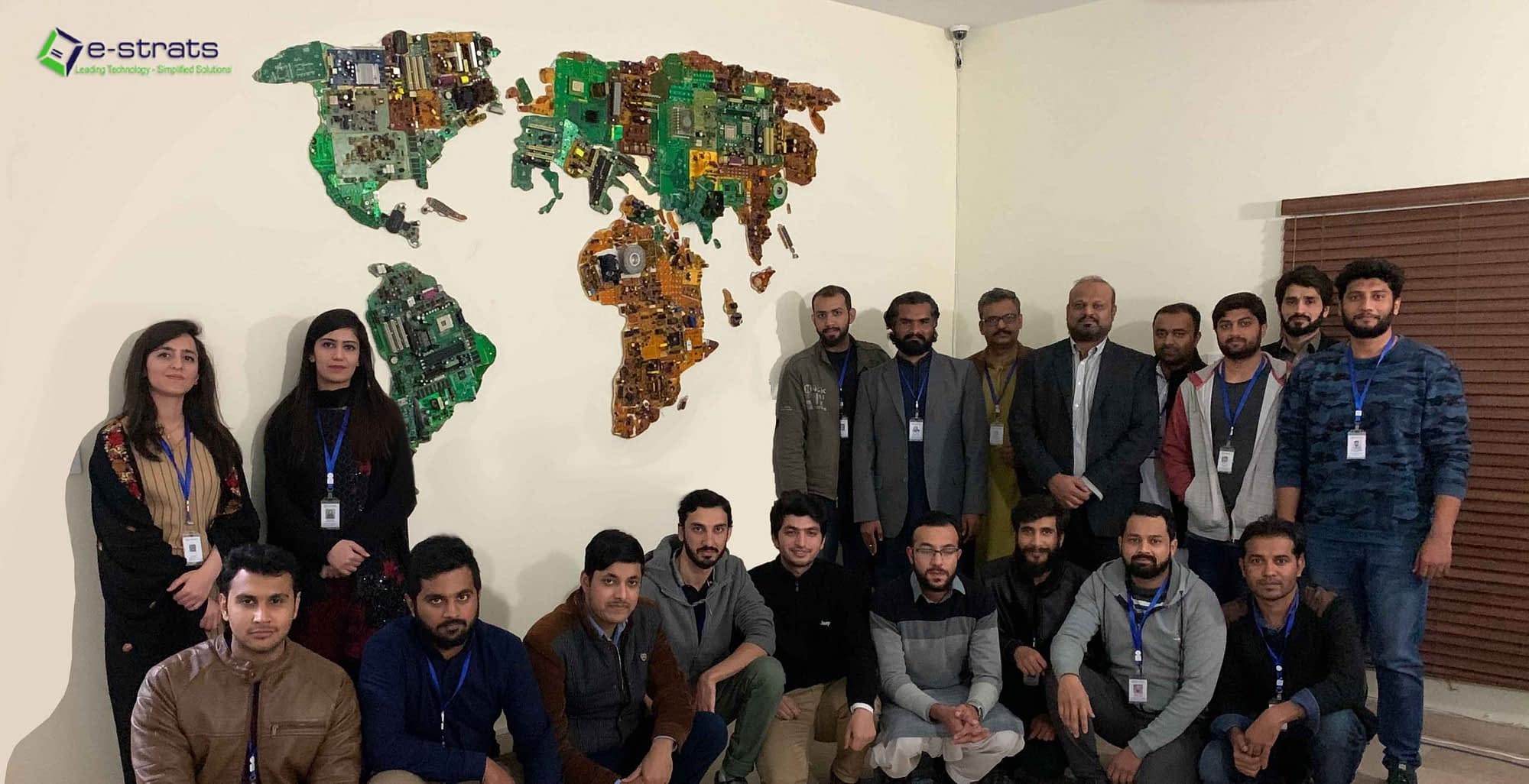team of e-strats IT company posing infront of a world map made out of e-scrap
